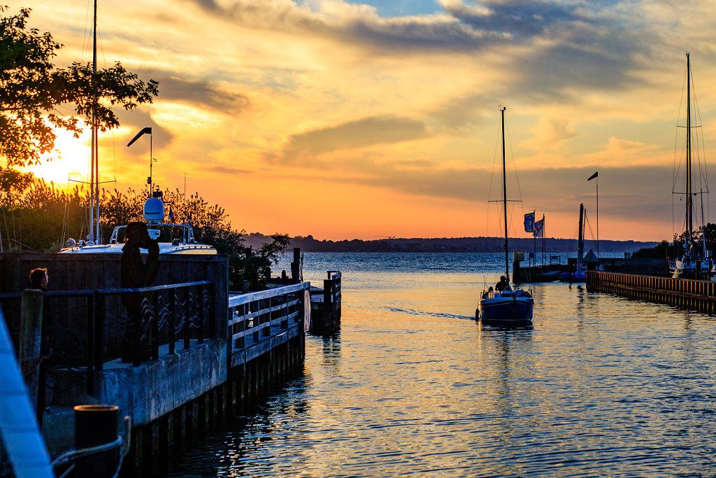 Segelschiff bei der Hafeneinfahrt bei Sonnenuntergang